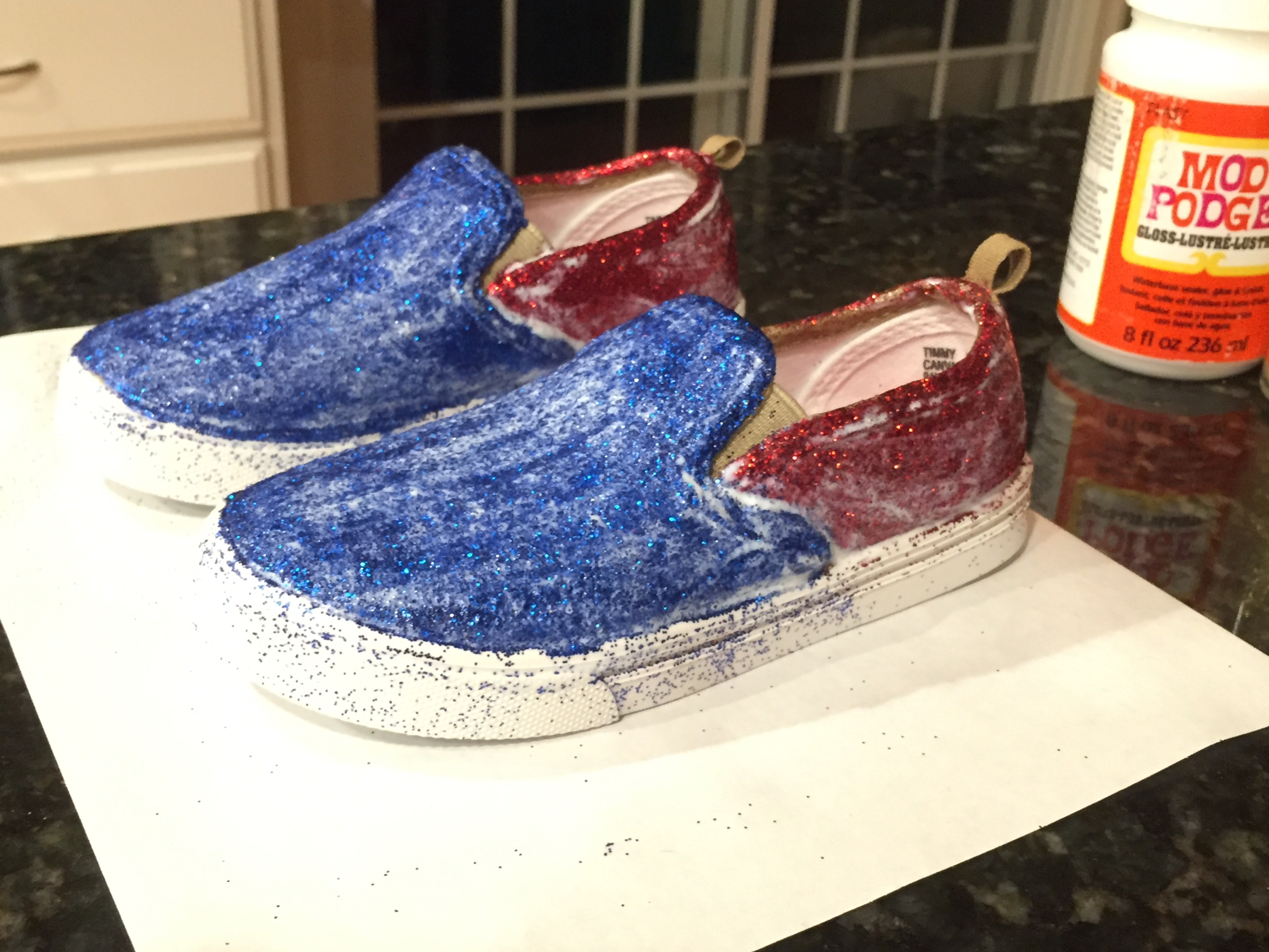 Once the last coat of glitter is dry and you're satisfied with the appearance of the shoes, you need to prepare the shoes for the sealant. If you got glitter anywhere you didn't want it, chip it off with your fingernails of wipe it away with a cloth dampened with hot water. Inspect your shoes.